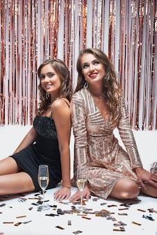 Jeunes filles élégantes s'amusant et buvant du champagne lors de la fête du nouvel an.