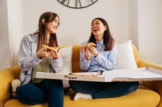 Jeunes filles excitées, appréciant la pizza
