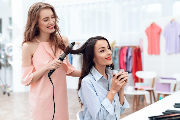Les jeunes filles font de la coiffure dans la salle d'exposition.