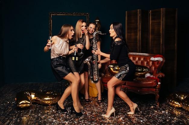 Jeunes filles gaies danser et boire du champagne pendant que leur copine joue