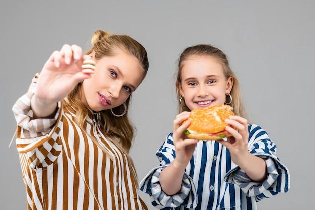 Jeunes filles gaies tenant un gros hamburger à deux mains tandis que sa sœur montre une version plus petite