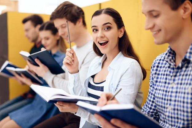 Les jeunes filles et les gars intelligents écrivent des idées dans le cahier.