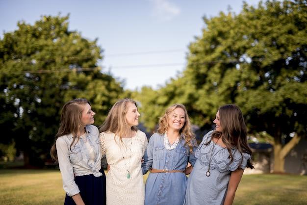 Jeunes filles heureuses les unes à côté des autres derrière les arbres