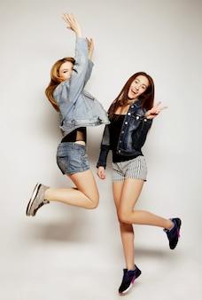 Jeunes filles hipster meilleures amies sautent