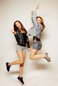 Jeunes filles hipster meilleurs amis sautent