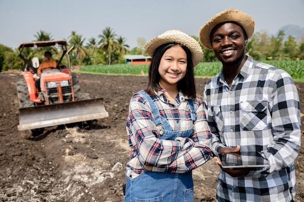 Des Jeunes Filles Ont Consulté Et Planifié La Plantation De Maïs Ou De Haricots Verts à L'aide D'une Tablette Informatisée Photo Premium