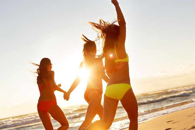 Jeunes filles profitant du soleil, du sable et de la mer