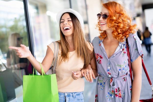 Jeunes filles séduisantes heureuses avec des sacs à provisions dans la ville.