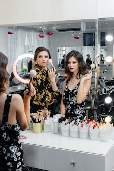 De jeunes filles sexy s'amusent et se maquillent pour une fête devant le miroir