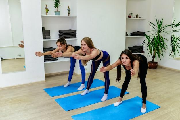 Les jeunes filles sportives attrayantes font du yoga ensemble.