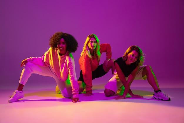 Jeunes filles sportives dansant le hip-hop dans des vêtements élégants sur fond rose-violet à la salle de danse en néon vert. concept de la culture des jeunes, du mouvement, du style et de la mode, de l'action.