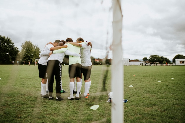 Jeunes footballeurs discutant de stratégie sur un terrain de football