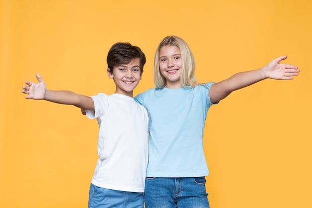 Jeunes frères et sœurs avec bras ouverts pour un câlin
