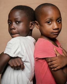 Jeunes frères et sœurs debout dos à dos