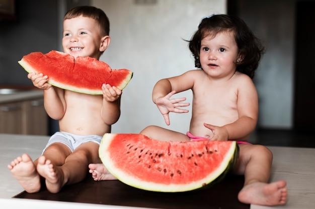Jeunes frères et sœurs mangeant des tranches de melon d'eau