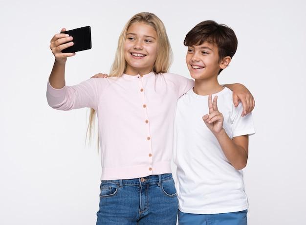 Jeunes frères et sœurs prenant des selfies