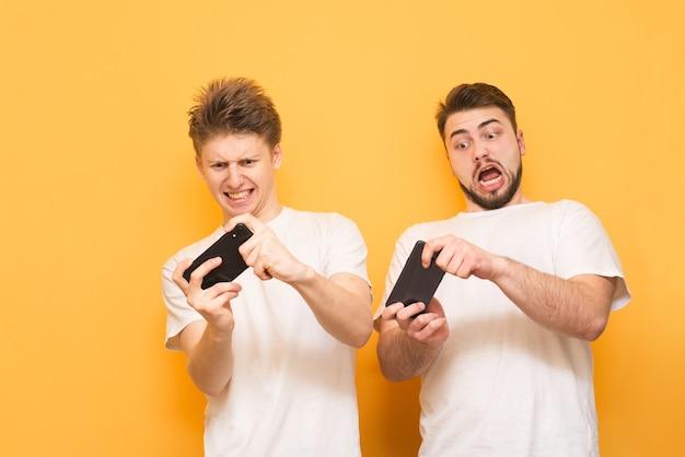 Jeunes garçons sur jaune portent un t-shirt blanc et jouent à des jeux sur smartphone