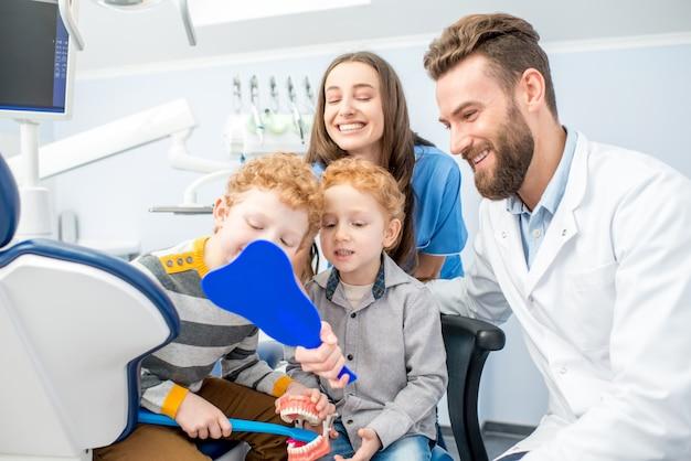 Jeunes garçons regardant le miroir avec un sourire à pleines dents assis avec un dentiste et une assistante au cabinet dentaire