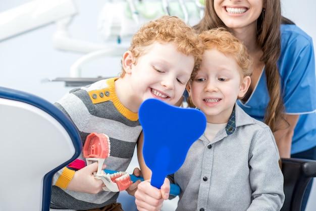 Jeunes garçons regardant le miroir avec un sourire à pleines dents assis avec un dentiste au cabinet dentaire