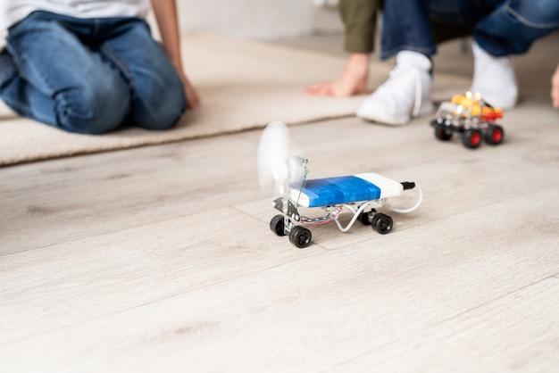 Les jeunes garçons et s'amusant à construire des voitures-robots ensemble à l'atelier