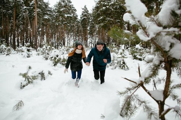 Les jeunes gars s'amuser dans la forêt par temps hivernal enneigé.