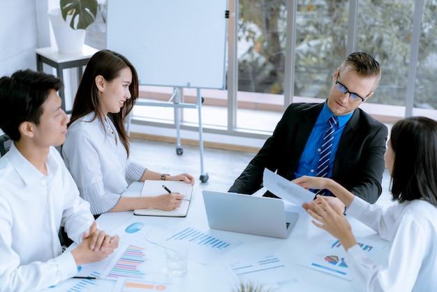 Jeunes gens d'affaires discutant des graphiques lors d'une réunion