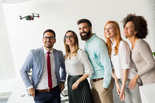 Jeunes gens d'affaires heureux laissant la caméra drone survoler le bureau et s'amuser