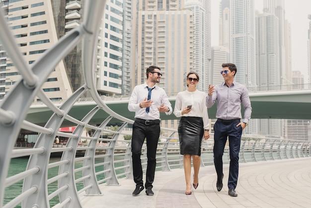Les jeunes gens d'affaires modernes en costume dans la marina de dubaï marchant vers leur bureau