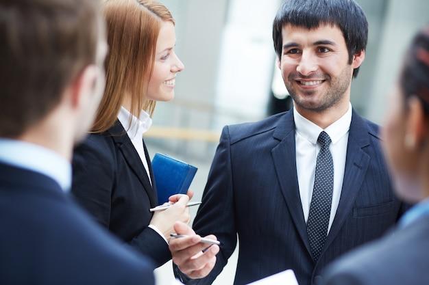 Les jeunes gens d'affaires de parler ensemble dans le bureau