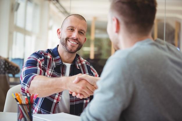 Jeunes gens d'affaires se serrant la main au bureau