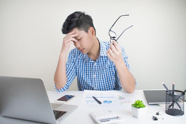 Les jeunes gens d'affaires sont stressés au travail alors qu'ils tiennent des lunettes sur leur bureau.