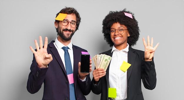 Les jeunes gens d'affaires souriant et à la recherche amicale, montrant le numéro quatre ou quatrième avec la main vers l'avant, compte à rebours. concept d'entreprise humoristique