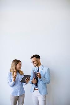 Jeunes gens d'affaires avec tablette numérique près du mur du bureau