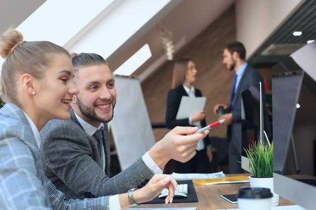 Jeunes gens d'affaires travaillant sur leurs ordinateurs de bureau dans les bureaux modernes.