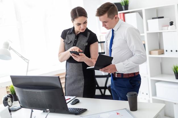 Jeunes gens au bureau en regardant l'écran du téléphone