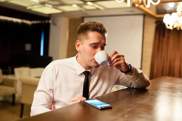 Jeunes gens buvant du café et regardant le téléphone