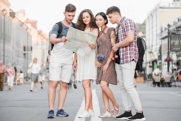 Jeunes gens debout sur la rue à la découverte de la carte de la ville