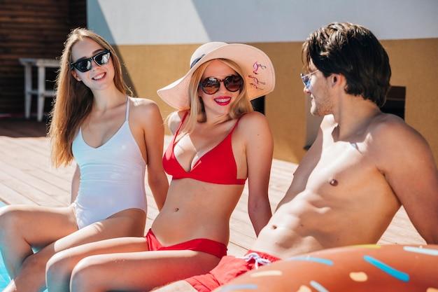 Jeunes gens discutant à la piscine