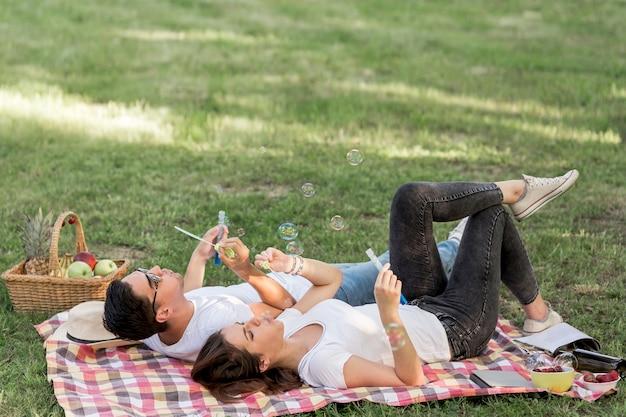 Jeunes gens faisant des bulles en position couchée sur une couverture