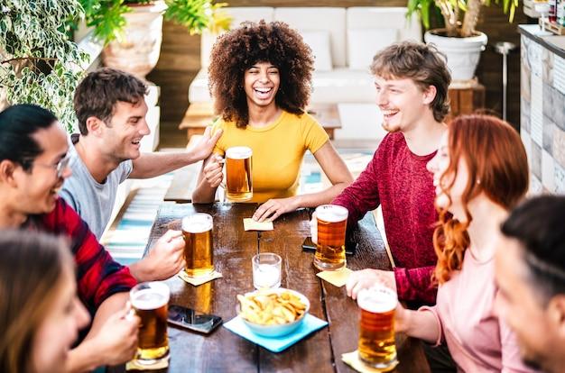 Jeunes gens de la génération z buvant de la bière à la terrasse du bar de la brasserie