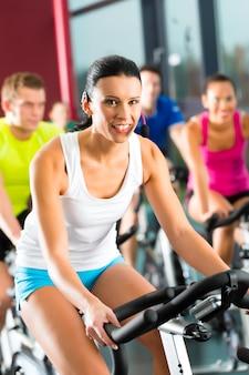 Jeunes gens, groupe de femmes et d'hommes faisant du sport spinning dans le gymnase pour fitness