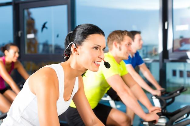 Jeunes gens - groupe de femmes et d'hommes - faisant du sport spinning dans le gymnase pour la forme physique