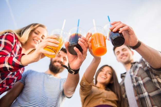 Les jeunes gens heureux boivent des boissons.
