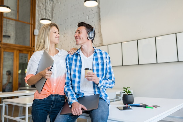 Jeunes gens heureux élégants au bureau de co-working,