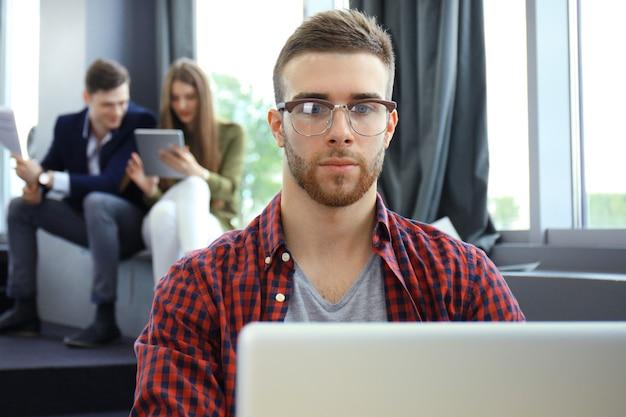 Les jeunes gens intelligents utilisent des gadgets tout en travaillant dur dans un bureau moderne. jeune homme travaillant sur son ordinateur portable.