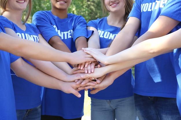 Jeunes gens mettant les mains ensemble à l'extérieur. concept de bénévolat