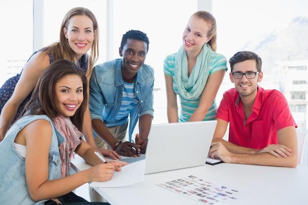 Jeunes gens occasionnels utilisant un ordinateur portable au bureau
