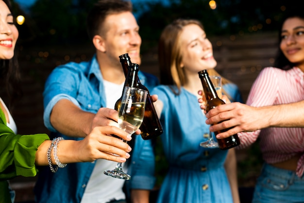 Jeunes gens portant un toast à des bouteilles de bière