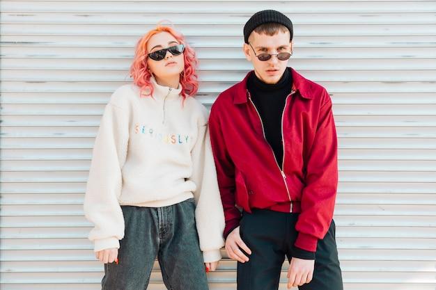 Jeunes gens posant avec des lunettes de soleil dans les vêtements de printemps chaud