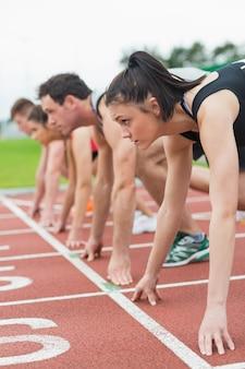 Jeunes gens prêts à courir sur le champ de la piste